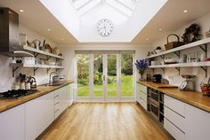 Wooden flooring and glass patio doors in modern kitchen extension with fitted white units - EWA Stock Photo Library
