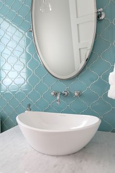 Blue glass tiles add dimension and a timeless appeal to this powder room.  Wall tile: Ann Sacks tile – Lucien Field Tile.    Countertop: Quartz Remnant.