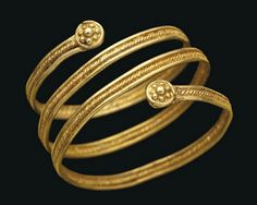 AN ETRUSCAN GOLD SPIRAL RING   CIRCA 7TH CENTURY B.C.   Composed of two smooth wires either side of a spirally twisted wire, terminals in the form of granular rosettes within a wire border  5/8 in. (1.6 cm.) diam.