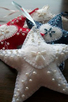 This whimsy star ornament is made with wool felt and craft felt. The star is white. They are hand stitched with a 100% cotton pastel pink and white embroidery floss. Sequins and glass beads and pearls are added for a splash of sparkle! The are lightly stuffed with poly-fill to make them a little poufy! A 7 satin ribbon hanger is attached. These can be used as bowl fillers, door hanger, ornaments for the holidays or added as gift package decoration. Great for babies first Christmas!    They…