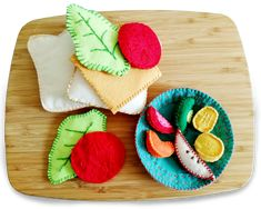 """This pattern allows you to hand sew a wide selection of felt food that is guaranteed to keep your children occupied. Foods included are vegetables, fruits, meat, bread and many more.    Instant download digital sewing pattern.    [accordion]    [accordion-item title=""""Features & Options""""]    Options     Plate   Tartlet   Dollop of whipped cream   Slices of bread   Cheese   Tomato   Meat   Banana   Apple   Kiwi   Strawberry   Chips   Lettuce leaf   Orange wedge   Pineapple chunk"""
