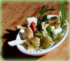Pasta…….maar dan als hapje op een prikker! Ingrediënten: • Farfalle, vlinder- of strikvormige pasta • rucola • potje gedroogde zontomaatjes • blok feta • oregano • dressing van 1 el frambozenazijn en 3 el olijfolie of wat olie van de zongedroogde tomaatjes en peper en zout Kook de pasta beetgaar, giet af en laat afkoelen. Snij de feta in blokjes en laat de zongedroogde tomaatjes uitlekken. Meng alles goed met de pasta. Neem een prikker, maak er een kleurrijk geheel van! #pastasalade