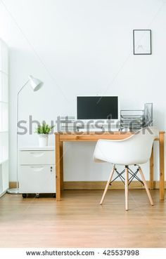 Spacious room with wooden floor with small space for work. By the wall wooden table with computer