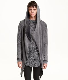Long sweatshirt cardigan with a raw-edge hood, diagonal zip at front, and side pockets. Raw-edge hem at hood and hem. Ribbing at cuffs.