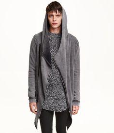 Long sweatshirt cardigan with a raw-edge hood, diagonal zip at front, and side pockets. Raw-edge hem at hood and hem. Ribbing at cuffs.