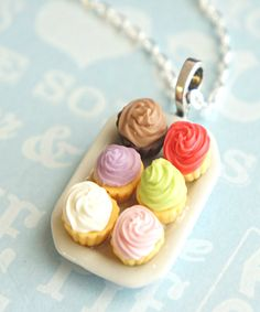 this necklace features a plate pendant of handmade cupcakes sculpted from polymer clay. the ceramic plate pendant measures 2.5 cm x 1.5 cm and is securely attached to a silver tone chain necklace that