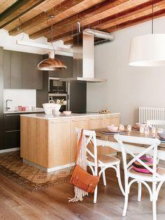 Cocina con isla en acabado madera y zona de cocción