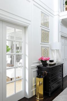 Chic foyer features stacked Jean Baptiste Geometric Prints placed over a black bamboo hall chest and tapered glass lamp placed next to a gold hexagon umbrella holder alongside a gray geometric runner.