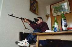 A Bosnian man takes aim at Serbian snipers in the mountains opposite his room on the 20th floor of a building in Sarajevo.