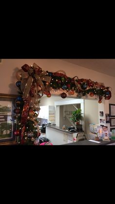 Receptionist  office Christmas swag over window area using multi-ribbon bow and loops and mixed ornaments. (Dr. Larry Downs office. November 23, 2015). Designed by Sidney Nicholson--Southern Traditions--Booneville, MS 662-728-1876