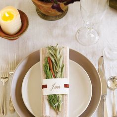 Rather than purchase season-specific tableware and decorations, simply accent what you already have. Adorn napkins with name cards, herbs, and a ribbon for a dash of holiday color.