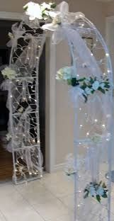 Nice Tule bows with lights and flowers on arch