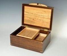 The figured, multi-colored patterns of the spalted Maple lid panel present a great contrast to the subtle, deep brown of the South American Walnut. Spalting occurs as a tree dies, and if the wood is captured at the right time, some greatly figured pieces can be salvaged. The box is approximately 12 1/2 x 8 1/2 x 6 high. the bottom level has a removable divider grid. Above that are two, sliding and removable trays. The premium hinges are solid milled brass with built in stops to hold the lid…