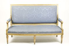 French, 19th century. Louis XVI style giltwood carved & upholstered settee, the rectangular back with entrelac carved frame to downswept arms with padded elbow rests, the bowfront seatrail similarly carved and raised on 6 turned, tapered and fluted legs headed with patera blocks.