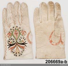 Ett par handskar för kvinna av vitt skinn. Såldes färdiga. Ingick bland de standardgåvor som fästmannen gav bruden  inför bröllopet. Ser i stort sett likadana ut över stora delar av landet.