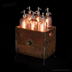 """Elecspritzity By AfterGlow Studio, these Six mismatched seltzer bottles are propped up and illuminated from within, look like their previous work """"Glassket"""