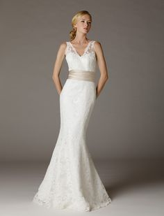 Celine              V-Neck wedding dress in an full length trumpet silhouette. Scalloped edges around neckline, armholes