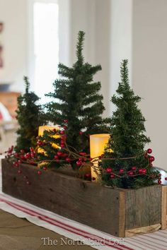 Mini Christmas trees, red berry garland, white candles in wooden box centerpiece