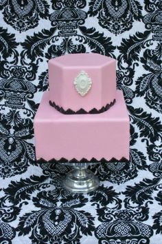 Simple yet elegant two tier square and hexagon design in pink, black, and white color tones featuring a molded fondant broach and trimmed in scalloped black fondant edging.