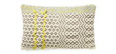 Das Panno Kissen ist aus gedeckten Farben zusammengesetzt und hat ein knallgelbes Zick-Zack-Muster.