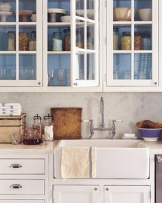 To compensate for the greenish cast of the glass and the shadowiness of these kitchen cabinets, the back of the cabinets are painted a warmer, clearer sky blue.Get the look with Martha Stewart Living Paint Color in Twilight at the Home Depot. Order a Tester of Twilight Paint Color