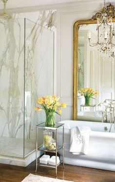 Marble shower, wood floor, large gilded mirror by tub.