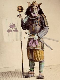 Samurai holding a sashimono, about 1875. by Felice Beato or Raimond von Stillfried.