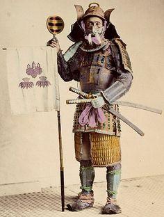 Samurai holding a sashimono, about 1875. by Felice Beato or Raimond von Stillfried.