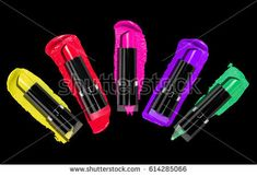 Palette of colorful lipsticks with cosmetic strokes on black background