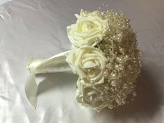 Something a bit different with strings of Ivory pearls wrapped around each other to form the top and surrounded by latex real touch roses.  An ivory satin handle finishes this bouquet beautifully.  All bouquets can be reproduced in the size and colour of your choice. Feel free to mix and match ideas to make your bouquet more individual. Corsage, MOB and Lapel pins are also available to match your colours. Contact leeann@bejewelledbridal.com.au for more information