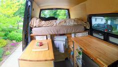 View in Sprinter van sitting in front swivel seat looking back. Ikea countertops on either side, utility drawer over fridge on drivers side, and storage with wire baskets underneath the countertops.