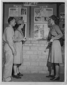 Evelyn E. Horton (right), Grace Hackenbury (left), and an unidentified serviceman pose in front of a WWII news bulletin board in 1944. Both women wear WAC summer service uniforms with handbags and hold sunglasses.