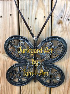 Junkyard Art by Tam-I-Am. Horseshoes, a masonry drill star punch, nuts and bolts come together as a butterfly. Scrap metal art.