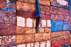 Una boiserie patchwork coloratissima realizzata con fasciame di vecchie #barche da pesca denominate #Gozzi che riprendono vita in altra forma. #falegnamo #opera