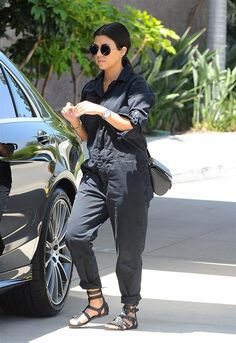 Kourtney Kardashian wears a black denim jumpsuit with a crossbody bag, gladiator sandals, and round sunglasses