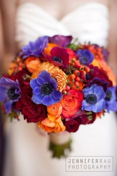 "deep red ""hearts"" roses, vivid purple anenomes, orange ranuncula, circus roses, and rose hips, and tangerine dahlias."