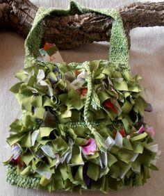 borsa di cotone a tracolla color verde mèlange, realizzata a uncinetto e decorata con nastri di tessuti pregiati tagliati a vivo e annodati uno ad ...