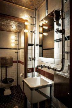 Odsłonięte rury, ozdobne żarówki stylizowane na przemysłowe i białe kafelki metro – klimat vintage industrialnej łazienki