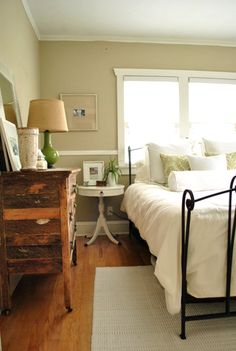 great paint color, love the iron bed frame with the fresh, white and green linens, side table & lamp, and especially the weathered wood dresser. Love!