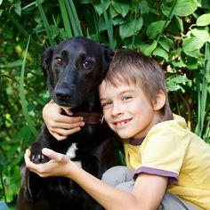 Boy hugs black puppy by Shutterstock