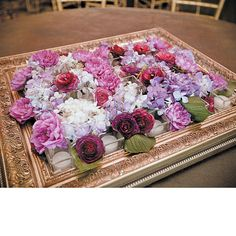 Brides.com: Unique Wedding Centerpieces. Wedding centerpiece of ranunculuses, hydrangeas, and dahlias arranged on a gilded frame by New Creations Flower Company, Royal Oak, MI Browse more pink wedding centerpieces.