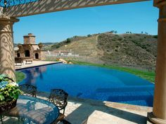This infinity pool features a contoured design bordered by an outdoor fireplace. Sweeping hillside views can be enjoyed from the pool's edge or from two Mediterranean-inspired patios.