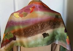 This silk scarf is hand dyed with beautiful autumn colors. - Handmade Silk Scarf - Hand Painted Silk Scarf How big is it? - 14 X 72 What materials and techniques are used? - Watercolor Dye - satin silk How do I care for it? - Hand wash gently in cold water with mild soap. - While the