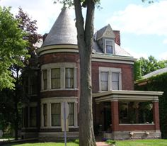 Built circa 1890, the brick Queen Anne-style Worthington Mansion  exhibits attention to detail, such as the full-height tower with curved windows. Other Queen Anne aspects include a complex roofline with slate shingles, and dentil molding along the roof and porch cornices, and the ornamental design on the gable of the  dormer window. The windows on the main façade, in clusters of two and three, are surrounded in stone with stone pilasters between each window and at the ends of each cluster.