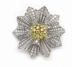 A colored diamond and diamond starburst brooch