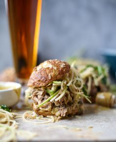 Smoky Pulled Pork Sandwiches with Spiralized Apple Slaw, maple Dijon mustard on pretzel buns. | How Sweet It Is