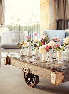 The low cocktail tables will have a trio of white bud vases filled with pale peachy-pink spray roses, queen anne's lace, peach stock flowers, and grey dusty miller surrounded by fluted votives.