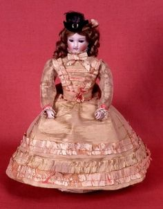 1875 Doll Culture: French Medium: bisque Doll with bisque head with inset blue eyes, fair styled hair in long ringlets, open mouth with two rows of teeth. Dressed in pink taffeta high necked dress and a little black velvet hat trimmed with grey ostrich feather and silver buckle. The body is contains a clockwork mechanism. The doll moves on three metal wheels on a wooden base.