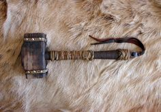 A handmade Viking war hammer is carved from redwood. The handle is hickory wood…