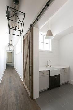 A Darlana Lanterns lights a rustic wood door on rails opening to a white and gray laundry room fitted with gray floor tiles accenting dove gray cabinets finished with satin nickel knobs and a white quartz countertop.